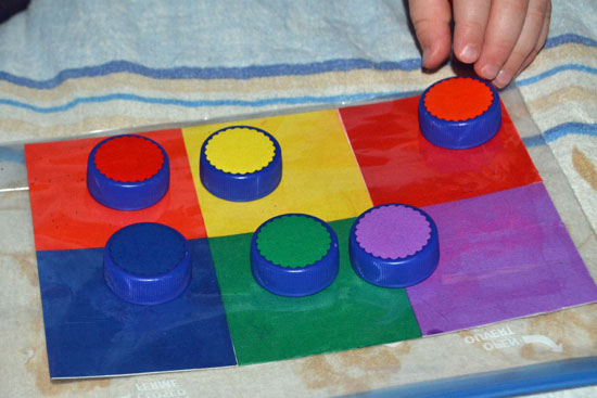 Make a simple DIY color matching game for your toddler using bottle caps.