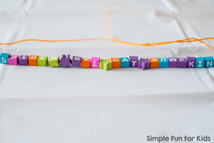 Literacy Activities for Preschoolers: Spelling Halloween words with beads and play dough! (Free printable included.)
