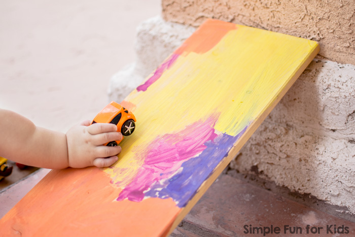 Try this super simple toddler science activity with your kids: First Toddler Play with a Ramp!