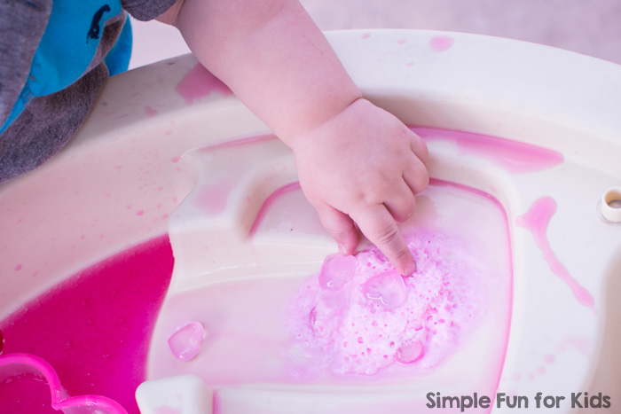 Super fun for toddlers and preschoolers on Valentine's Day or any day: Simple Baking Soda, Vinegar, and Hearts Sensory Play in the water table (or a sensory bin), perfect for siblings or play dates.