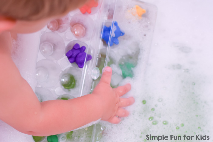 Toddler playing with colorful rainbow bears in a plastic egg carton in the bathtub.