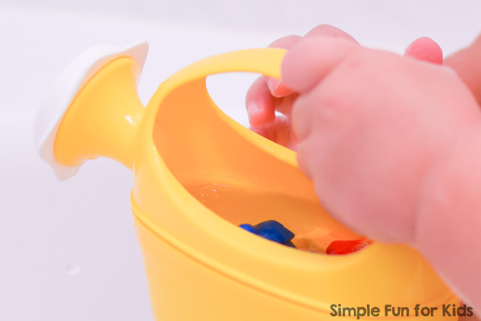 Toddler playint with colorful rainbow bears and a yellow watering can in the bathtub.