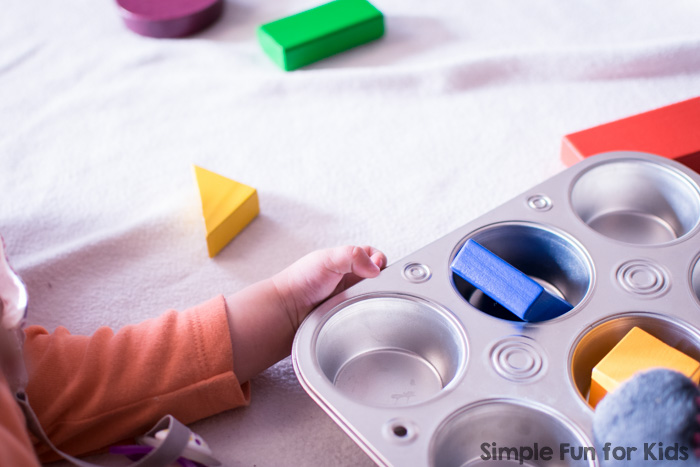 Our little friend played with this simple set up for a long time practicing fine motor skills: Baby Play with Wooden Blocks in a Muffin Tin